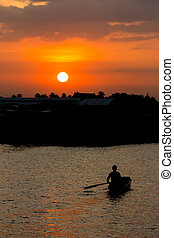 Rowing man in boat at sunset