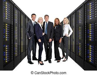 Businessteam standing on front of server racks -...