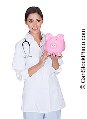 Young Female Doctor Holding Piggy Bank. Isolated On White