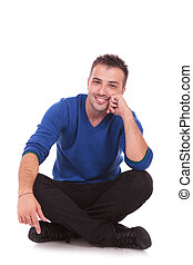 young casual pensive man sitting with legs crossed and...