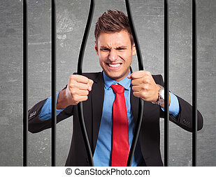 businessman bending the bars of his prison - angry strong...