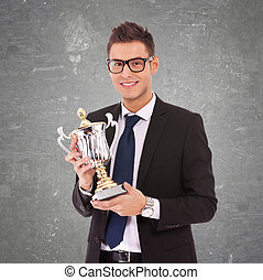 business man with glasses holding a big trophy - young...