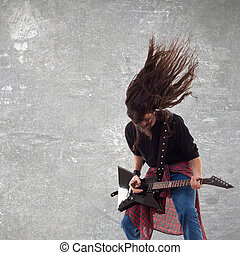 headbanging electric guitar player on gray background...