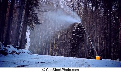 Snow cannon in winter forest - Creating a ski slope with a...
