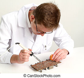 working electronics repairing board using soldering pen on a...