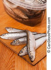 salted anchovies in box on wooden background