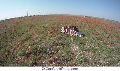 In a poppy field - Four women looking for something in a...