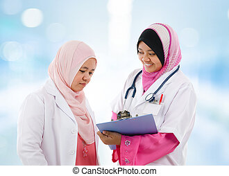 Two Southeast Asian Muslim medical doctor discussing on...