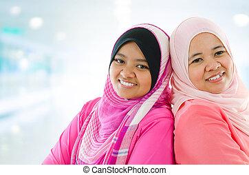 Happy Muslim women standing inside house. Two Southeast...