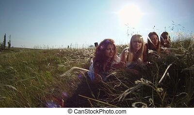 Four women posing for a camera in a field