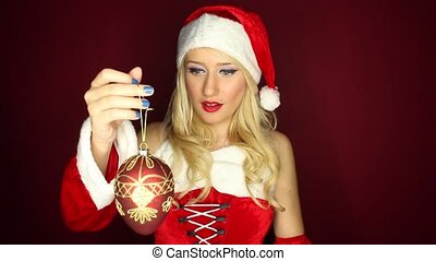 Santa girl plays with tree ornament