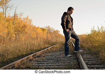 Melancholy - A man outside standing on some tracks, in a...