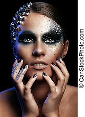 Portrait of woman with artistic make-up isolated over black...