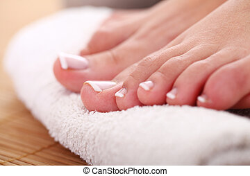 Beautiful foot with french pedicure on white towel