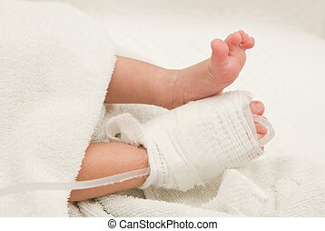Intra venous fluid line at foot of new born patient