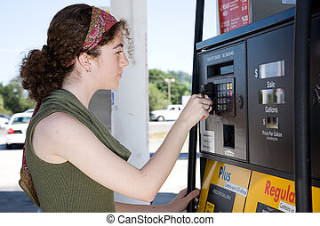 Buying Gas - Young woman uses her credit card to pay for...