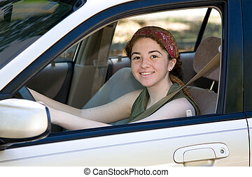 Happy Teen Driver - Pretty teen driver smiling behind the...