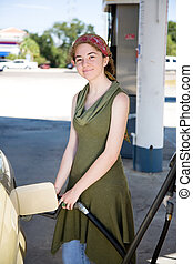 Happy with Fuel Efficiency - Young woman filling up her gas...