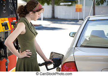 Pumping Gas - Teen girl at the gas station filling up the...