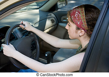 Serious Young Driver - Teen girl concentrates on learning to...