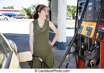 Shocked by Gas Prices - Young woman filling up her gas tank...