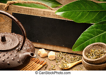 Asian tea set and rustic wooden board with copyspace