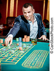 Gambler stakes playing at the casino table