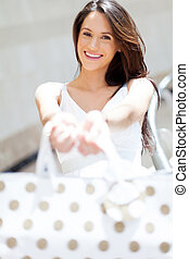 cheerful young woman holding shopping