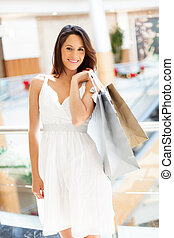 woman carrying shopping bags in mall - attractive young...