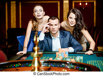 Man with two ladies playing roulette at the casino