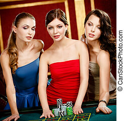 Three girls place a bet playing roulette