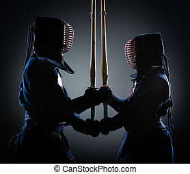 Two kendoka opposite each other with wooden sword Japanese...