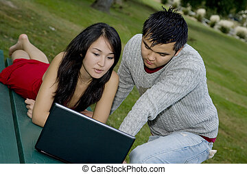 Asian - Asain couple studing using a computer at a park