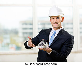 Engineer pointing at model house