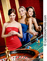Women with glasses of spirits play roulette - Women keeping...
