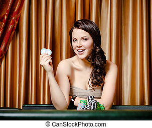 Female gambler at the roulette table with chips - Portrait...