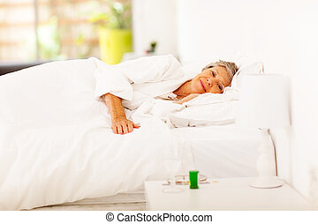 senior woman resting on bed at home