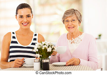 woman having tea with grandmother - beautiful young woman...