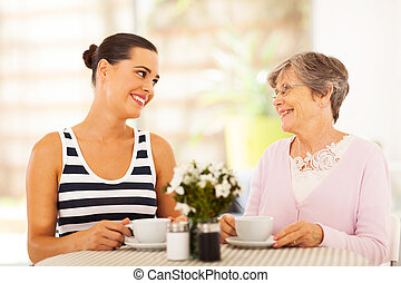 young woman visiting senior mother and having coffee...
