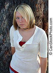 Shy - Serious young blond woman looking upward with a shy...