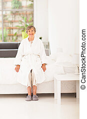 happy elderly woman in pajamas sitting on bed