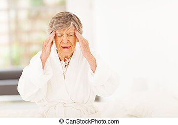 senior woman feeling headache at home