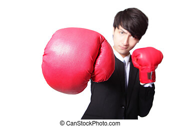 Business man fighting with boxing gloves (focus on glove)...