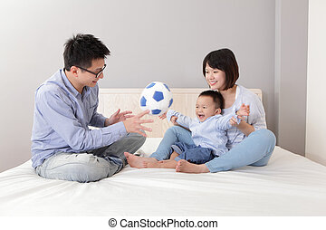 happy family playing toy soccer on white bed in the bedroom...