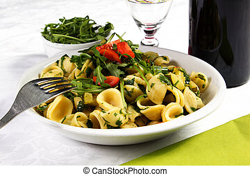 orecchiette, with rucola salad and tomatoes on the white...