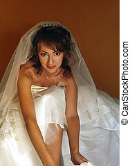 Beautiful bride - The laughing bride puts on stockings