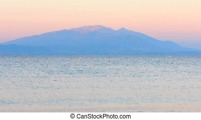 Blue sea surface with mountain