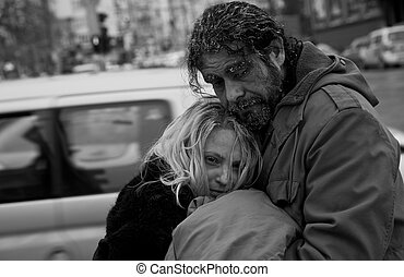 b/w homeless couple embracing - Black and white image of...