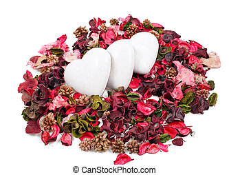 three gingerbread hearts in the background of sachet petals