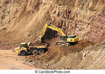 Backhoe and dumptruck at rock quarry - A Backhoe and...